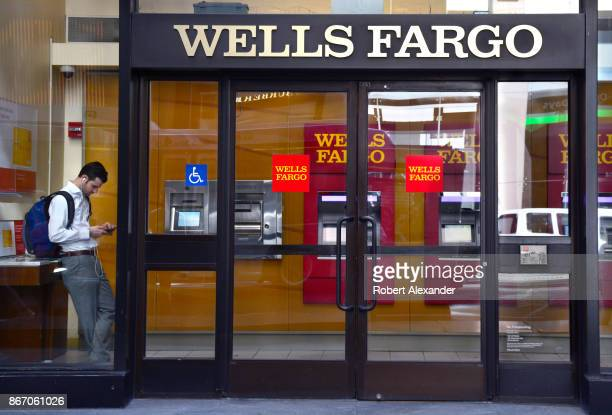 A man uses his smartphone inside the lobby of a Wells Fargo branch bank in New York New York