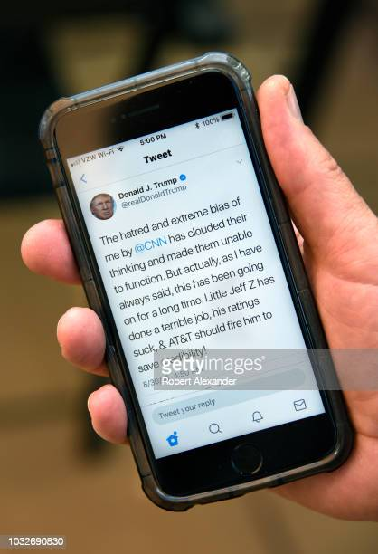 A man uses his smartphone to read a tweet from US President Donald Trump attacking CNN and the television network's president Jeff Zucker for alleged...