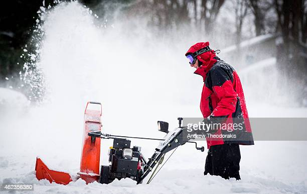 A man uses his snowblower to clear his driveway and the road following a major snow storm January 27 2015 in Stony Brook New York Much of the...