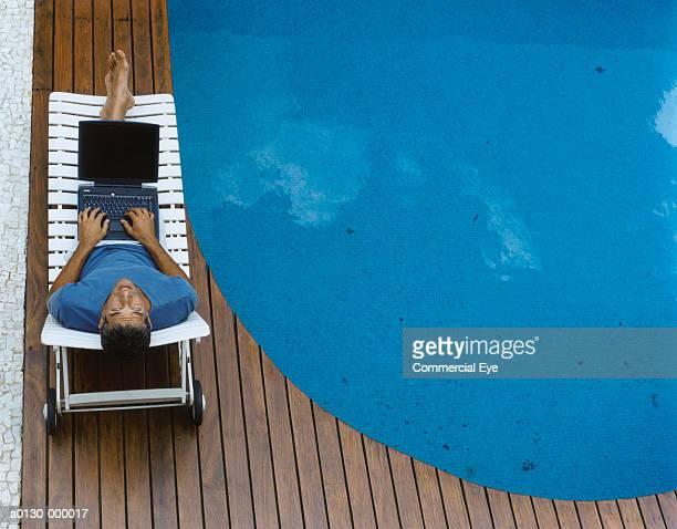 Man Uses Laptop Near Pool