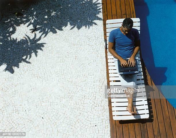 man uses laptop near pool - human body part - fotografias e filmes do acervo