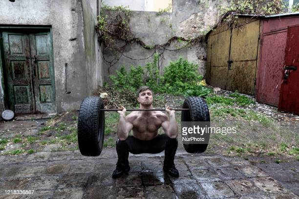 Man uses old tires and a carpet hanger during his sport training in an old unequipped backyard to keep fit during coronavirus pandemic in provincial...