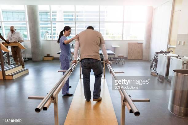 l'uomo usa barre parallele nel centro di riabilitazione - convalescenza foto e immagini stock