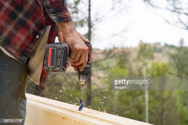 man uses power tool to drill into unfinished log cabin in colorado - printed sleeve stock pictures, royalty-free photos & images