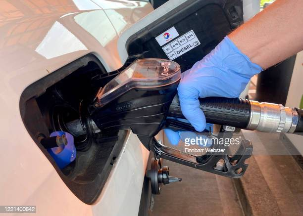Man uses protective gloves whilst filling a car with fuel at a petrol station on April 27, 2020 in Weymouth, United Kingdom. The British government...
