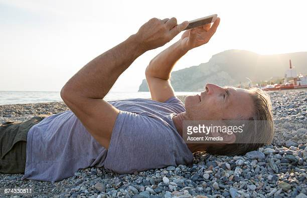 Man uses smart phone while lying on beach