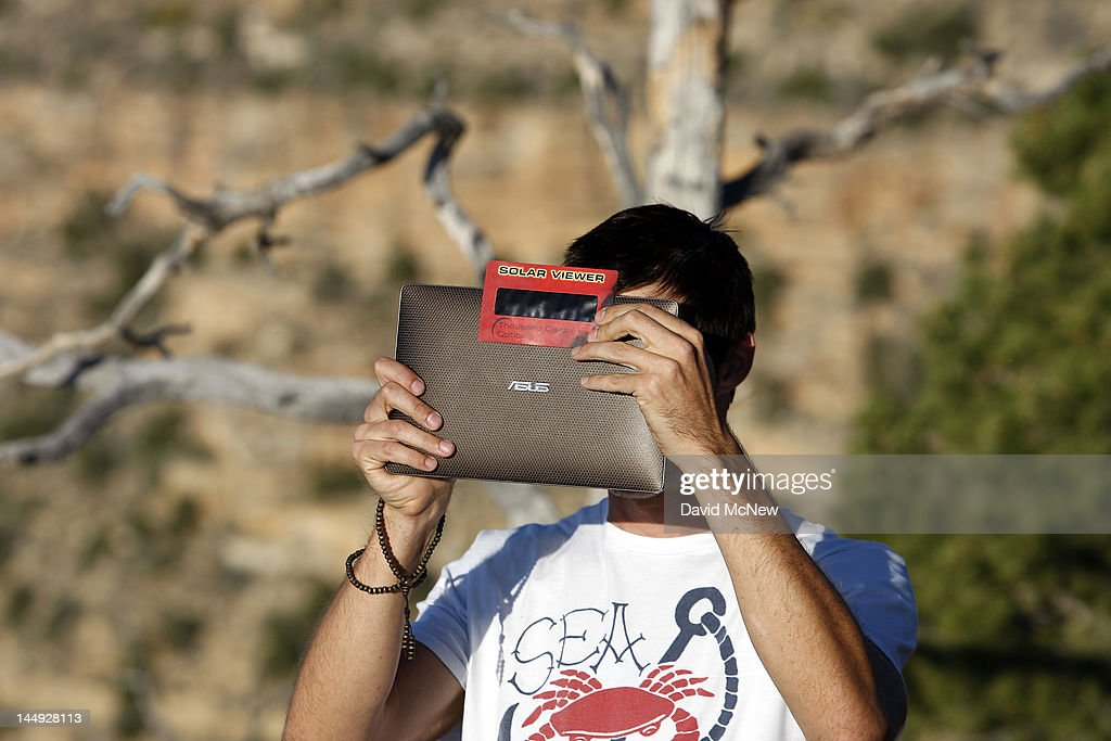 A man uses solar film over the lens of his electronic device to photograph the first annular eclipse seen in the U.S. since 1994 on May 20, 2012 in Grand Canyon National Park, Arizona. Differing from a total solar eclipse, the moon in an annular eclipse appears too small to cover the sun completely, leaving a ring of fire effect around the moon. The eclipse is casting a shallow path crossing the West from west Texas to Oregon then arcing across the northern Pacific Ocean to Tokyo, Japan.