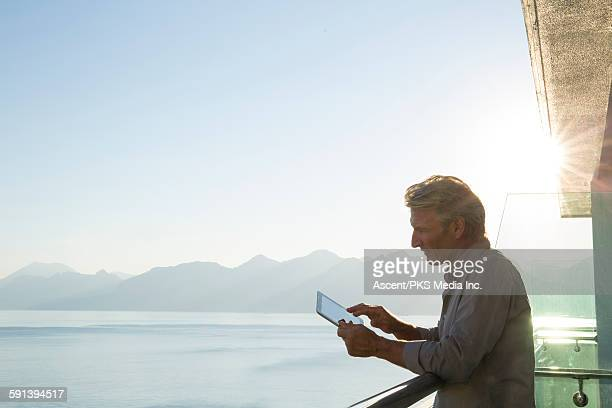 Man uses ipad on hotel deck, overlooking sea