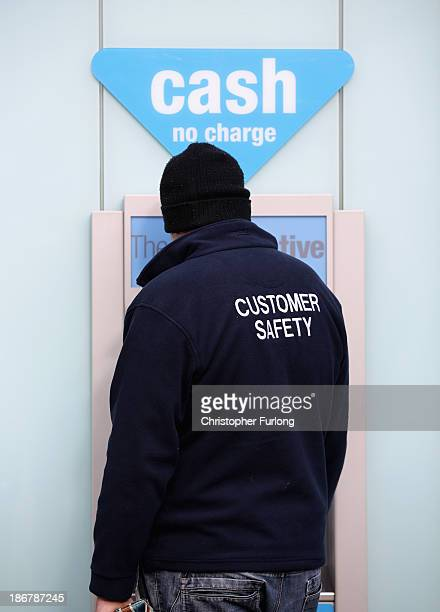 A man uses the cashpoint machine at the Crewe branch of the Cooperative Bank on November 4 2013 in Crewe United Kingdom The Cooperative Bank has...