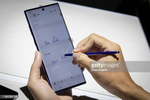 A man uses the stylus on the new Samsung Galaxy Note 10 smartphone during a launch event at Barclays Center on August 7 2019 in the Brooklyn borough...