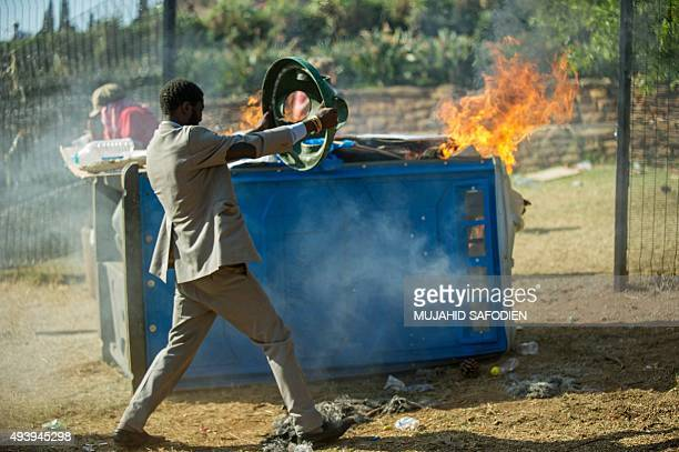 A man uses the top of a trash can for protestion from rubber bullets as during clashes between students and police in front of the Union Building on...
