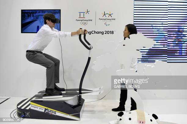 Man uses virtual reality glasses at the 2018 Pyeongchang Winter Olympics stand during the International Tourism Fair in Madrid on January 17, 2018.