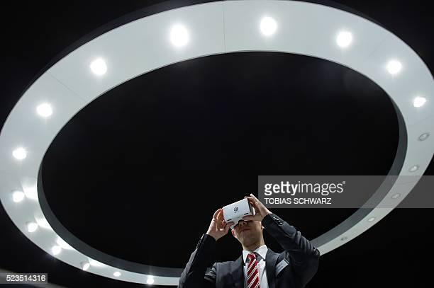 A man uses virtual reality glasses at the booth of German car maker Volkswagen on the eve of the opening of the 'Hannover Messe' in Hanover northern...