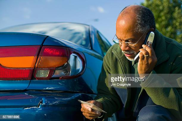 Man Using a Cell Phone Beside His Scratched Car