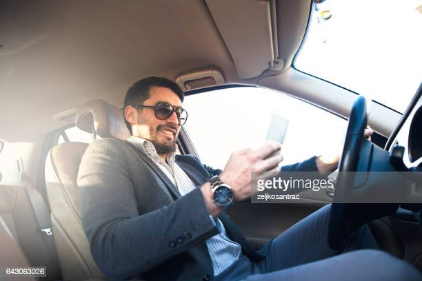 Man using a cell phone in his car