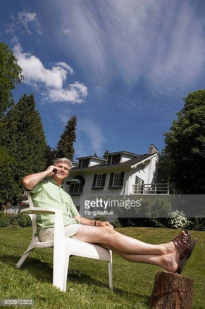 Man using a cell phone in his yard