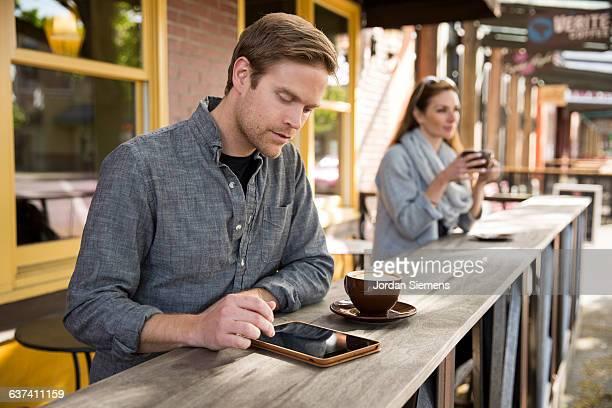 A man using a digital tablet at a coffee shop.