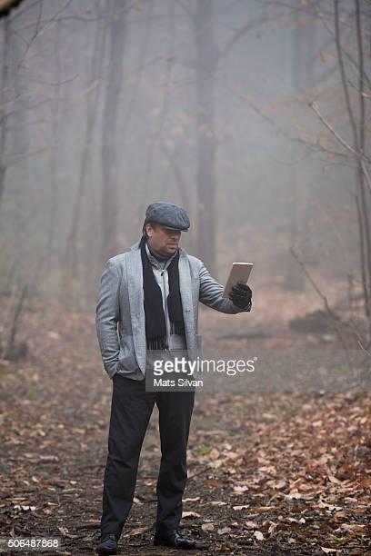 Man using a digital tablet in the forest