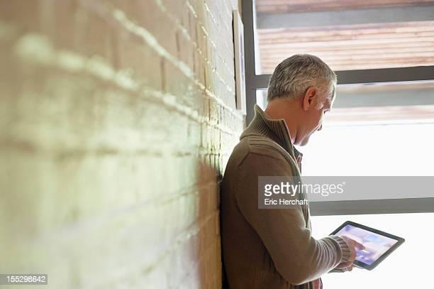 Man using a digital tablet near a window