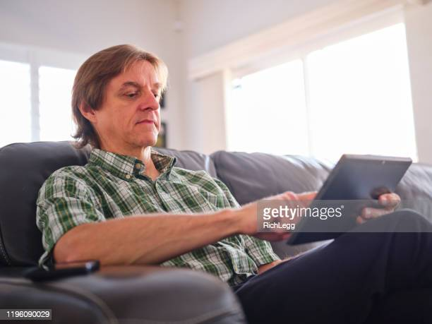 man using a digital tablet - rich_legg stock pictures, royalty-free photos & images