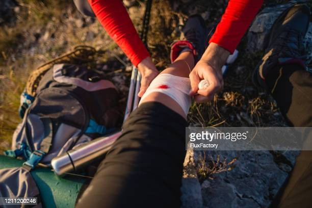 man using a first aid kit on an injured woman in the mountains - wounded stock pictures, royalty-free photos & images