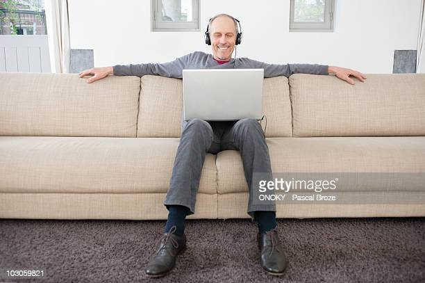 Man using a laptop and listening to music