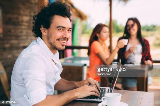 Mann mit einem Laptop in einer Strandbar