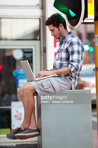 man using a laptop near traffic light - onoky stock-fotos und bilder