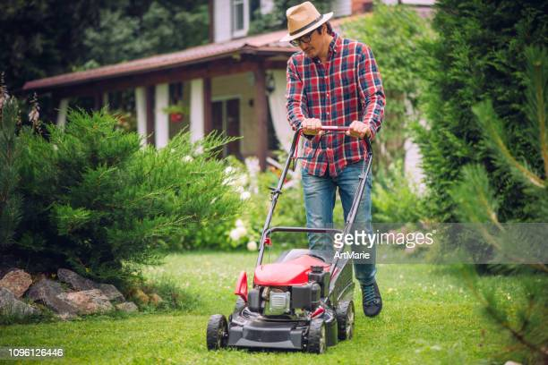 man using a lawn mower in his back yard - lawn mower stock pictures, royalty-free photos & images