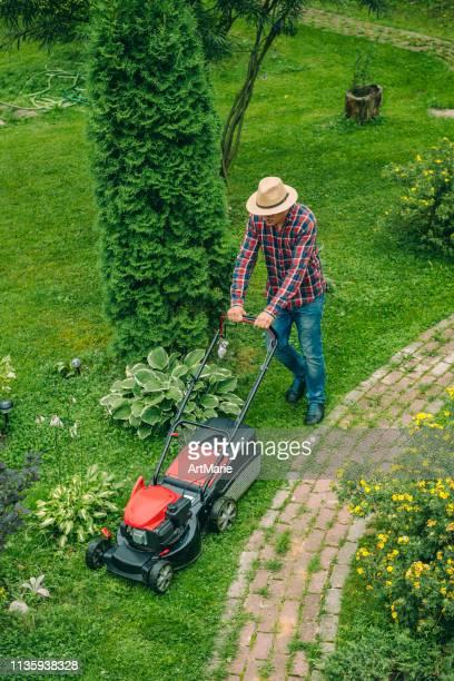 裏庭で芝刈り機を使っている男 - 造園師 ストックフォトと画像
