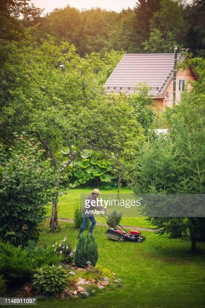 彼の裏庭で芝刈り機を使用して男 - 造園師 ストックフォトと画像