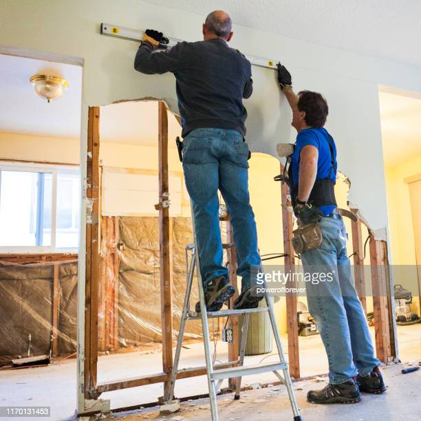 man using a level during home renovations - powerofforever stock pictures, royalty-free photos & images
