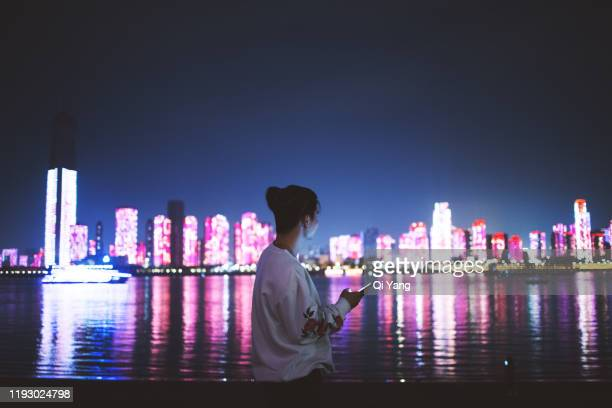 man using a mobile phone in the city at night - wuhan stock pictures, royalty-free photos & images