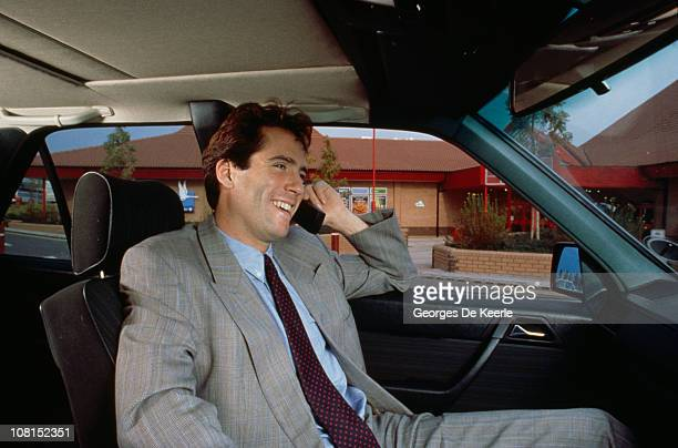 A man using a mobile phone in the passenger seat of a car circa 1990