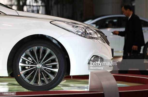 A man using a mobile phone walks past a Hyundai Motor Co 5G Grandeur sedan on display in the showroom at the company's headquarters in Seoul South...