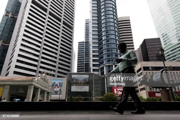 A man using a mobile phone walks past commercial buildings in the central business district of Singapore on Wednesday June 13 2018 Tourism as well as...