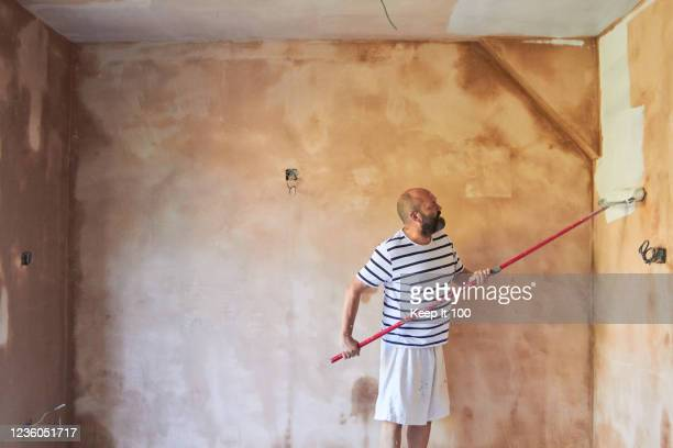 man using a paint roller - satisfaction stock pictures, royalty-free photos & images