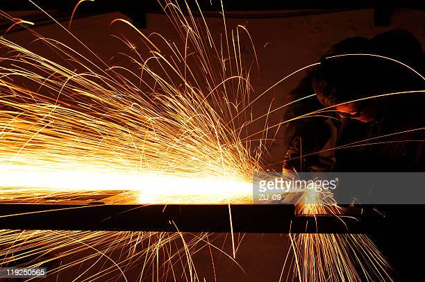 Man using a plasma cutter with sparks flying everywhere