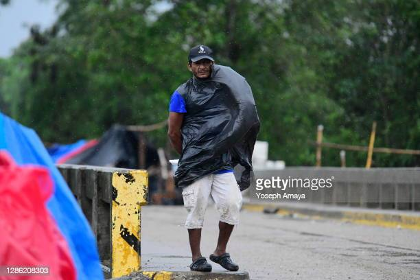 A man using a plastic bag to protect from the rain surveils an area of Barrio San Juan to protect the shelters and belongings of evacuated families...