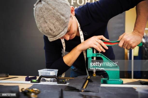 a man using a rivet machine, pressing hard on the handle at a workbench. - rebite ferramenta de trabalho imagens e fotografias de stock