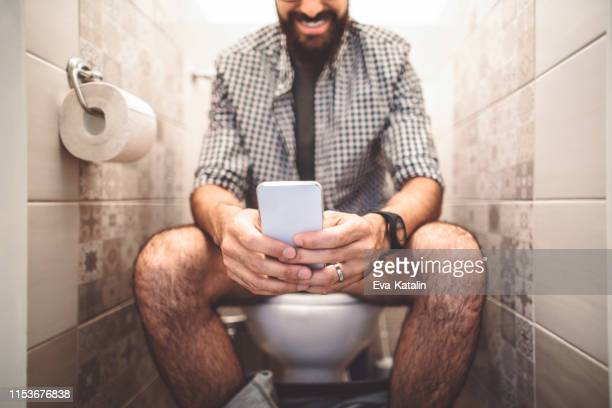 man using a smart phone while sitting on the toilet - defecare foto e immagini stock