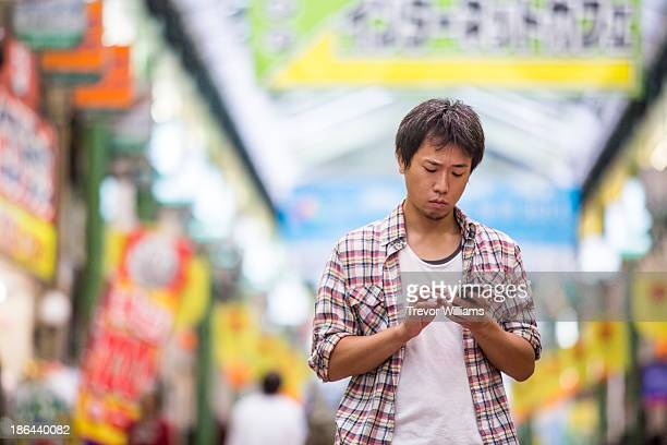 A man using a smartphone in a shopping area