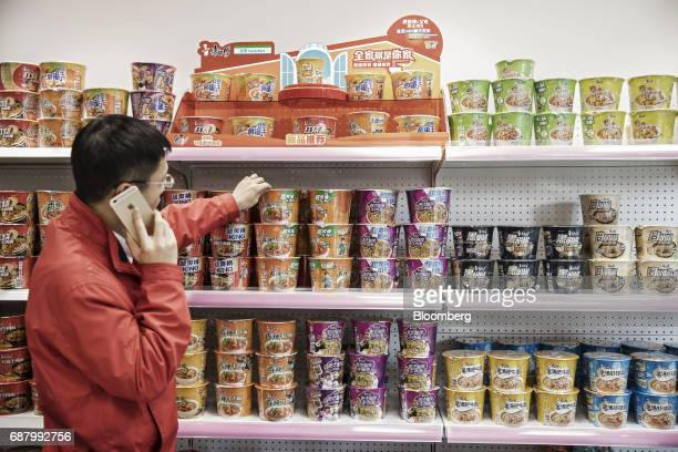 A man using a smartphone looks at various flavors of Tingyi Holding Corp Master Kong branded instant noodles packets sitting on shelves at the...
