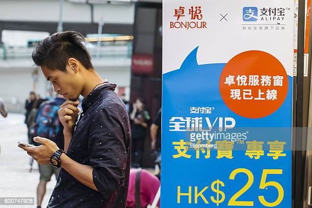 A man using a smartphone stands next to an advertisement for Ant Financial Services Group's Alipay an affiliate of Alibaba Group Holding Ltd outside...