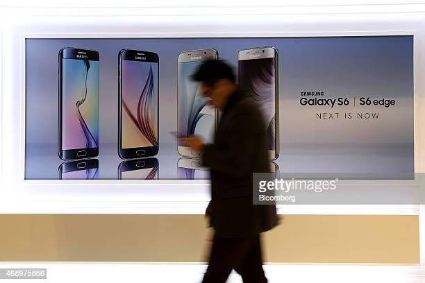 A man using a smartphone walks past an advertisement for Samsung Electronics Co Galaxy S6 and Galaxy S6 Edge smartphones during a launch event in...