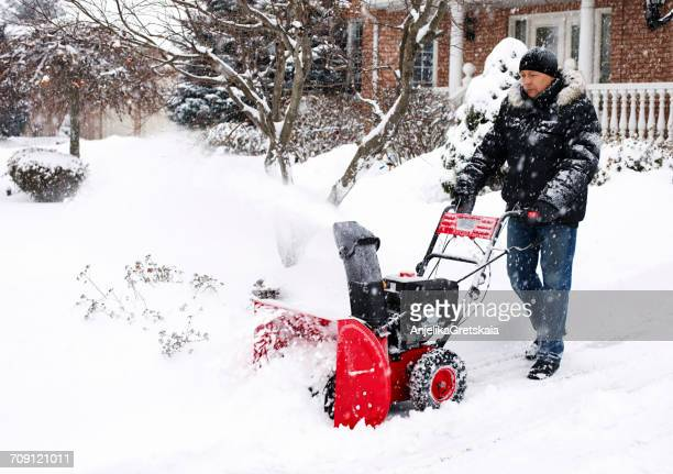 Man using a snow blowing machine, Canada