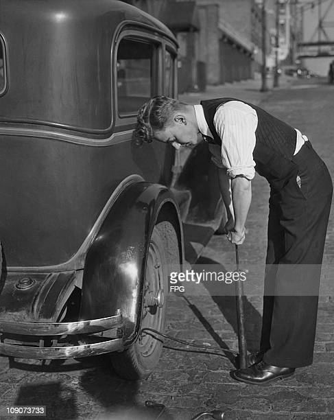 A man using a stirrup pump to inflate the rear tyre of a car circa 1925