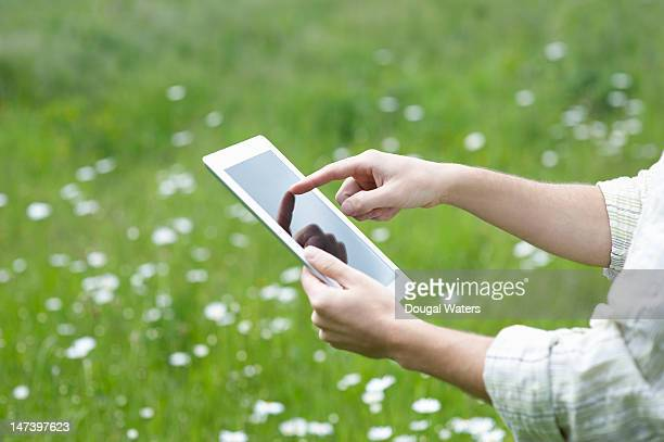 man using a tablet in a country meadow - newtechnology stock pictures, royalty-free photos & images