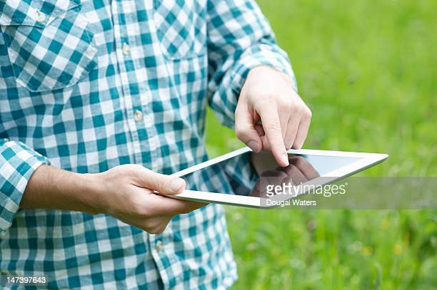 Man using a tablet in a summer park