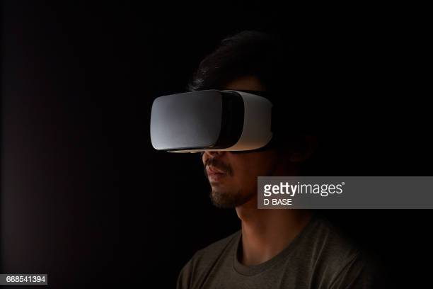 man using a virtual reality headset - simulatore di realtà virtuale foto e immagini stock